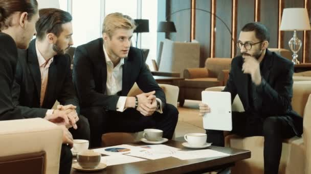 Four businessmen discussing a deal at business meeting in the modern restaurant. 4K