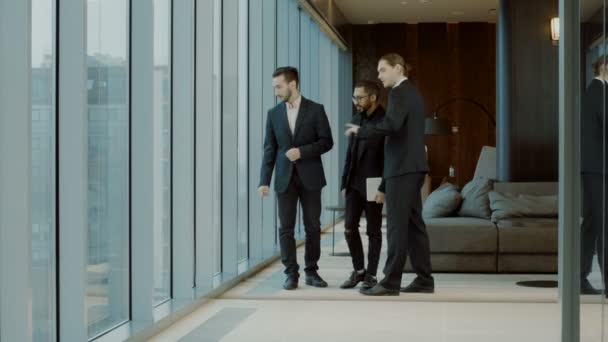 Three businessmen in business suits standing in front of big panoramic window, talking, beginning to dance, stopping and talking again. 4K