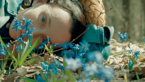 Close-up shot of young dark woman lying on the lawn with bluebells in the spring forest. 4K