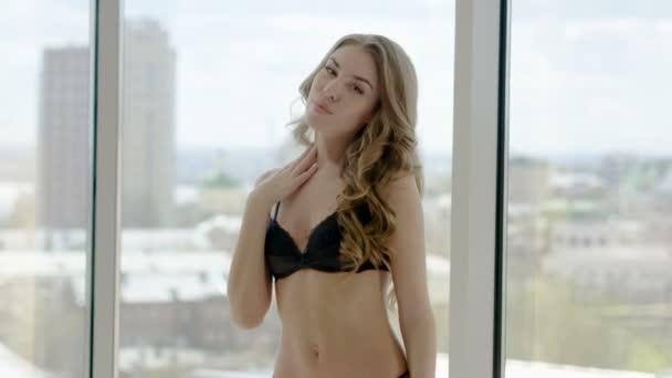 Krásná blondýnka mladá žena v černém prádle stojící na panoramatické okno v luxusně zařízeném pokoji. 4k