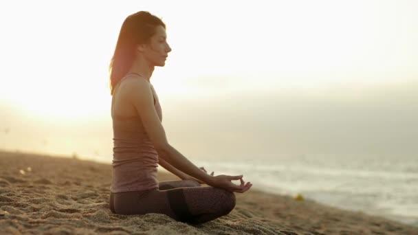 Küste der Costa del Maresme. junge kaukasische Frau in Sportbekleidung, die bei Sonnenaufgang Yoga am Sandstrand in der Nähe des ruhigen Mittelmeeres praktiziert. Calella. Barcelona. Spanien. Zeitlupe. hd
