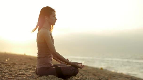 Pobřeží Costa Del Maresme. Mladá běloška ve sportovním oblečení relaxuje cvičením jógy na písečné pláži poblíž klidného Středozemního moře při východu slunce. Calello. Barcelona. Španělsko. Zpomal. Hd