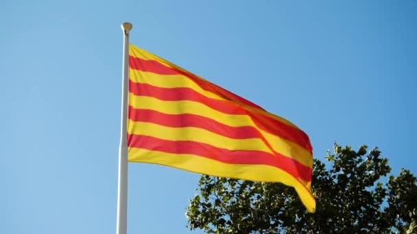 Közelkép Katalónia zászlójáról, amint a szélben integet a kék ég felé. Barcelonában. Spanyolországba. Lassú mozgás. Hd.