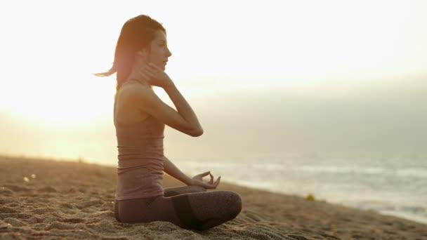 Nahaufnahme einer schönen Frau, die sanft atmet, in Lotus-Pose sitzt und am Sommermorgen spirituelles Yoga am Mittelmeer praktiziert. Calella. Barcelona. Spanien. Zeitlupe. hd