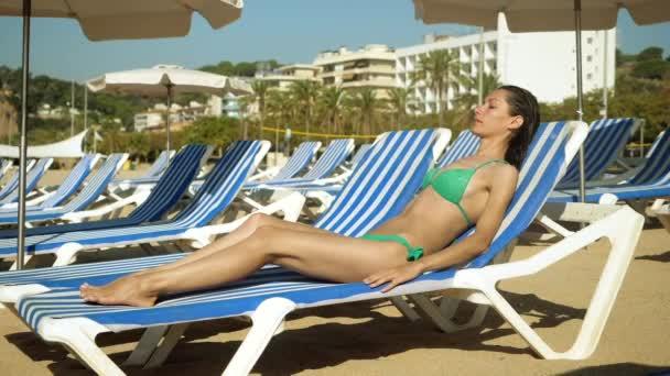 Fiatal nő karcsú test fürdőruhában fekszik a napozóágyon és napozik a Földközi-tenger partján. Spanyolországba. Lassú mozgás. Hd.