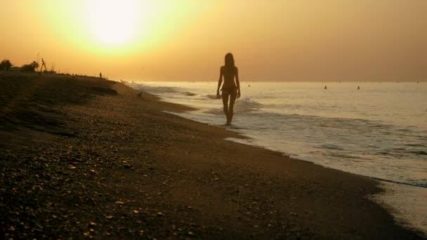 Pobřeží Costa del Maresme. Mladá krásná žena v plavkách kráčí bosá po písčité pláži Středozemního moře za úsvitu. Španělsko. 4k