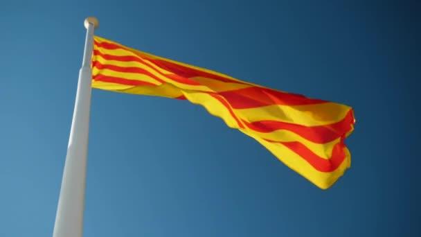 Közelkép Katalónia zászlójáról, amint a szélben repül a kék ég felé. Barcelonában. Spanyolországba. Lassú mozgás. Hd.