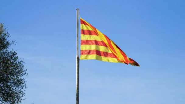 Közelkép Katalónia zászlójáról, amint a szélben repül a kék ég felé. Barcelonában. Spanyolországba. 4k