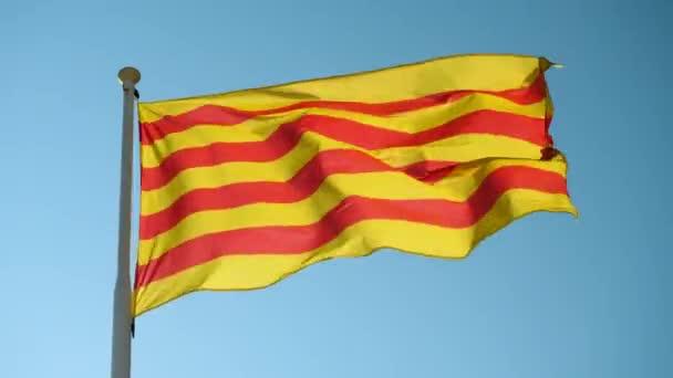 Közelkép Katalónia zászlójáról, amint a szélben integet a kék ég felé. Barcelonában. Spanyolországba. 4k