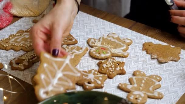 Közelkép női kezekről, ahogy cukormázas sütit tesznek a mézeskalácsra. 4k