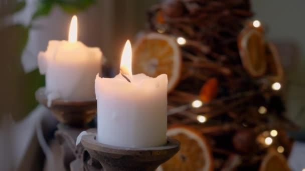 Dvě zářící bílé vánoční svíčky s jedlí a rozmazanými jiskřícími světly v pozadí. 4k