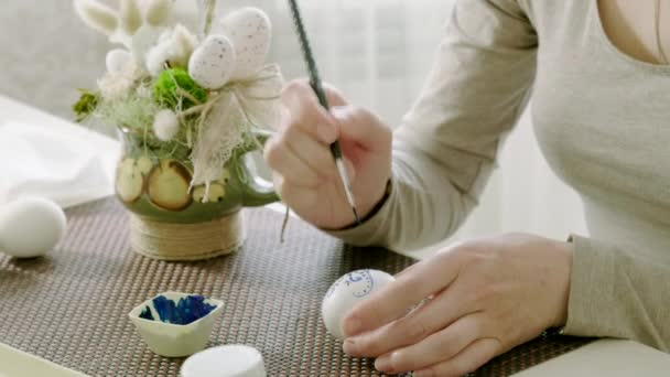 Close-up of woman painting chicken eggs for Easter holiday. 4K