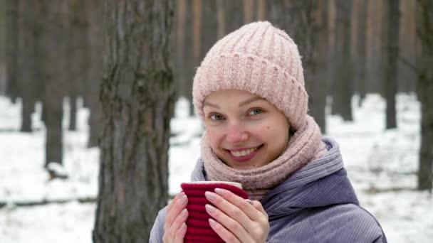 Christmas holidays. Close up of beautiful girl enjoying winter outdoors with a mug of hot drink. 4K