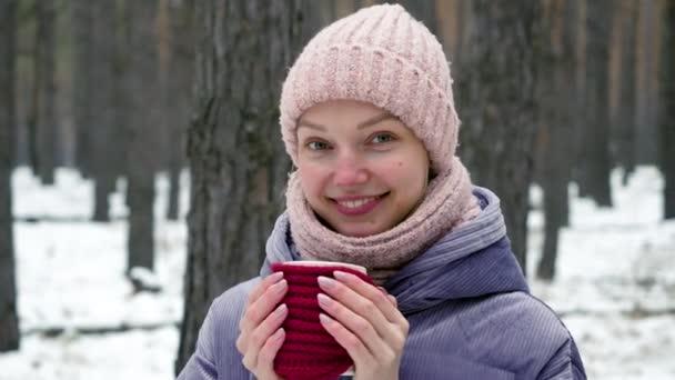Detailní záběr mladé usměvavé krásné dívky v zimním oblečení drží v ruce šálek horkého čaje v borovém lese. 4k