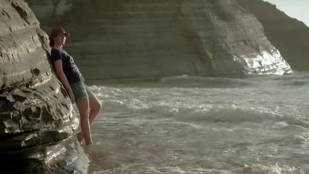 Krásná běloška se opírá o skálu na pobřeží Středozemního moře a zamyšleně se dívá do kamery. Řecko. 4k
