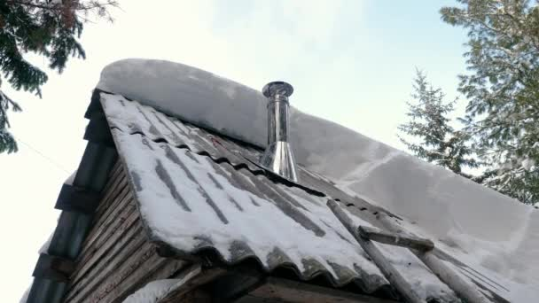 Close-up shot of smoke coming from a chimney on the roof of an residential building in a Siberian village. Metal smokestack on the rooftop of a house in Siberia. 4K