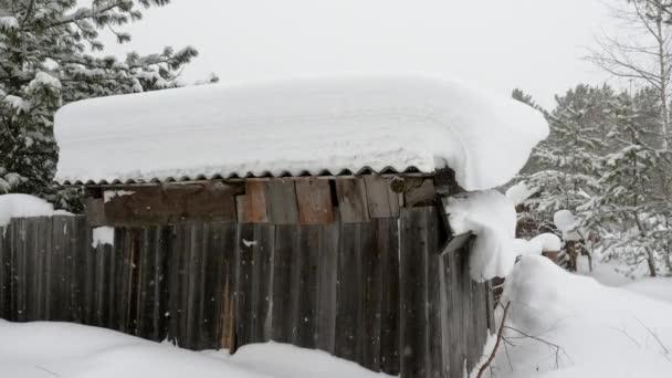 Zimní krajina. Vnější pohled na dřevěnou chatu pokrytou sněhem v ruské vesnici na Sibiři. Rusko. 4K