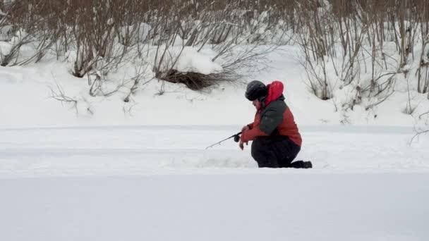 Jéghorgászat. A horgász a fagyott folyón horgászik. Egy ember, aki édesvízi halat fog télen. 4k