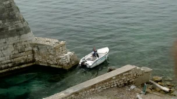 Das Boot segelt durch den Kanal entlang der alten Festung in Griechenland. 4k