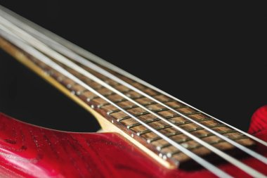 Red electric bass guitar with four strings on dark background