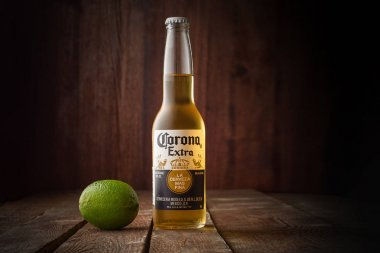 Editorial photo of Corona beer with lime on dark wooden background with copy space