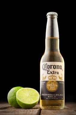 Editorial photo of Corona beer with lime on wooden table isolated on black. Copy space