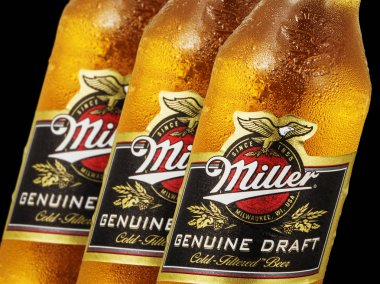 Editorial photo of close-up Miller Genue Draft Beer bottles isolated on black.