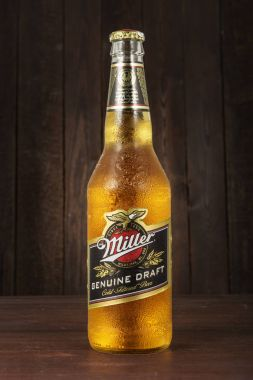 Editorial photo of Miller Genue Draft Beer bottle with drops on dark wooden background