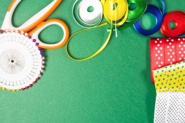 Scissors, pins and color tapes on green background