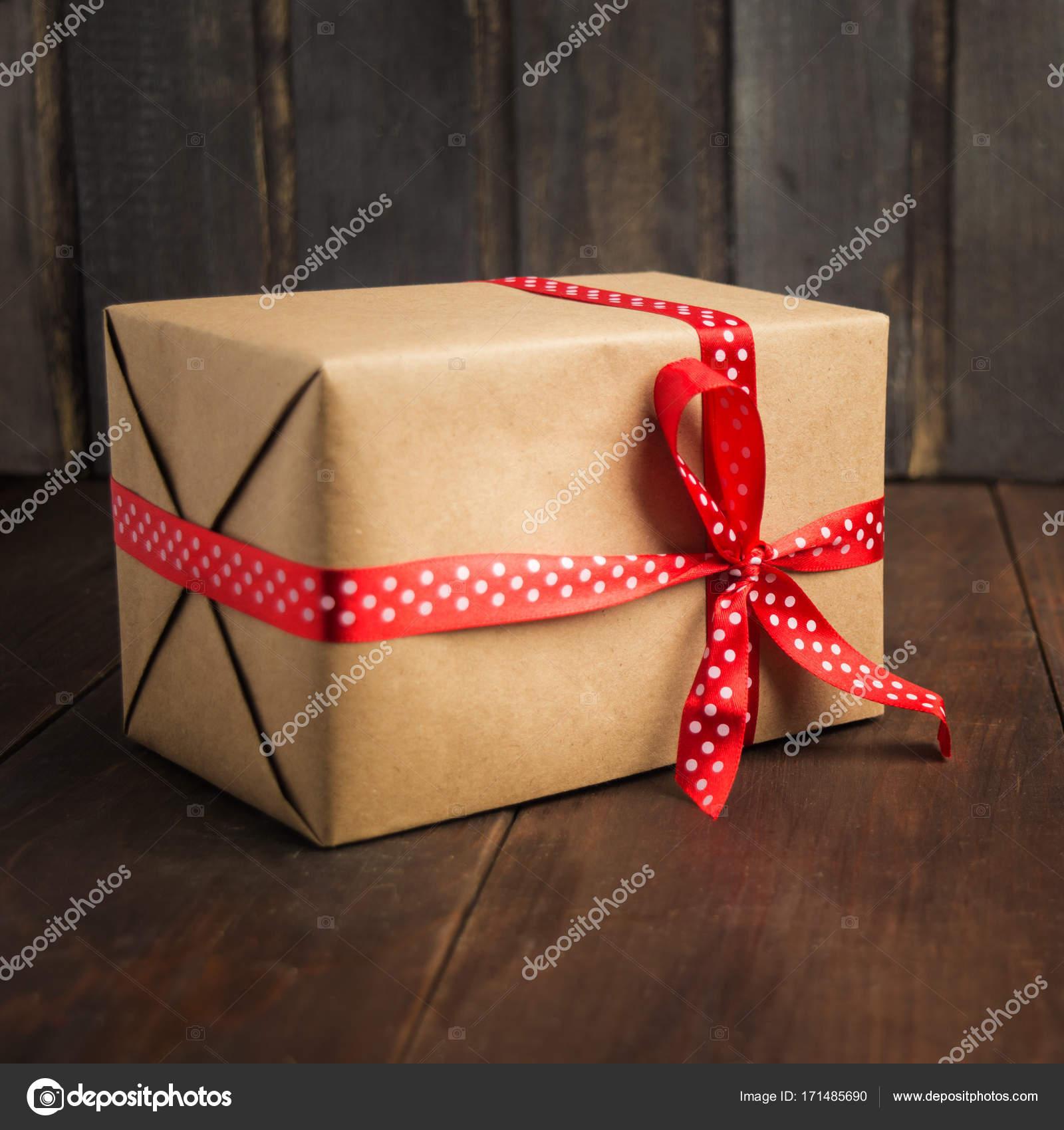 eb00c10a9138 Artisanat en papier présent avec ruban rouge sur un fond en bois marron —  Photo