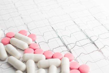 Pills in corner over paper cardiogram