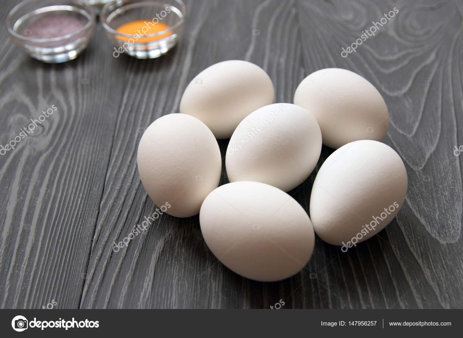 Weisse Hühnereier und Farbstoffe auf einem grauen Tisch Farbe ...