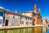 Az utcában csatorna és színes házak egy kis olasz város, Comacchio (Little Venice) kilátás. San Camillo Kórház (Múzeum, a római hajó) ellen a tiszta kék ég, Emilia-Romagna, Olaszország