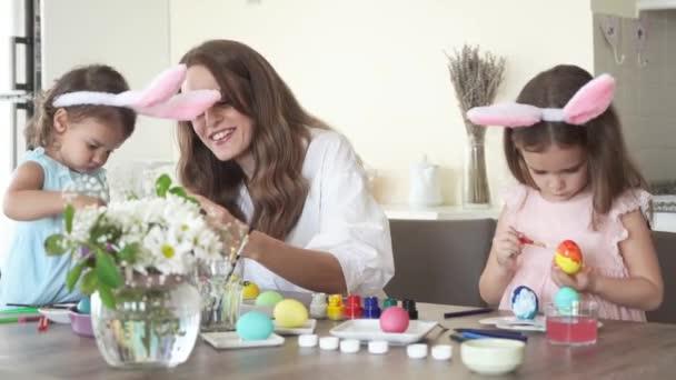 Šťastná rodina se připravuje na Velikonoce. matka s dcerami s legrační králičí uši malování velikonoční vejce dohromady, 4K.