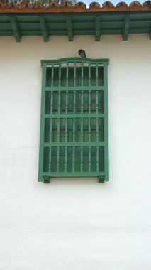 Green wooden window on white wall with tile roof