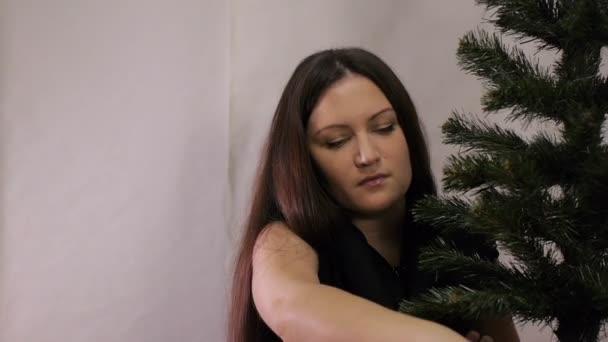új év, karácsony nő díszíti a karácsonyfát
