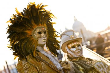 Couple of masked people in gold posing during traditional Venice Carnival