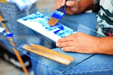Painter painting blue image