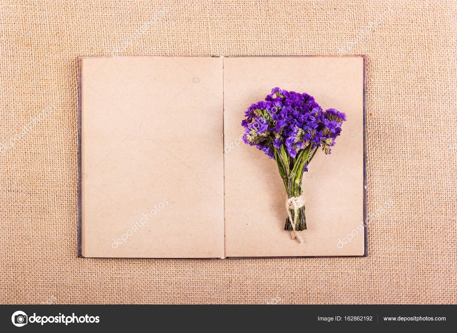 Un libro con páginas en blanco y un ramo de flores de color púrpura ...