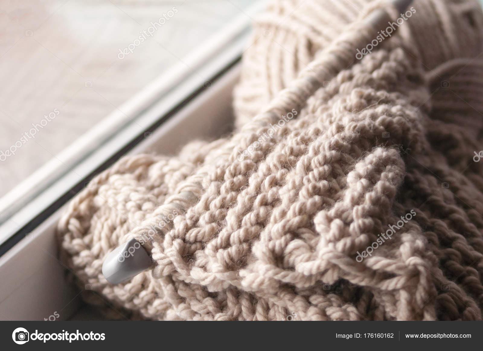 Una bufanda tejida con un hilo grueso en gruesas agujas color beiges ...