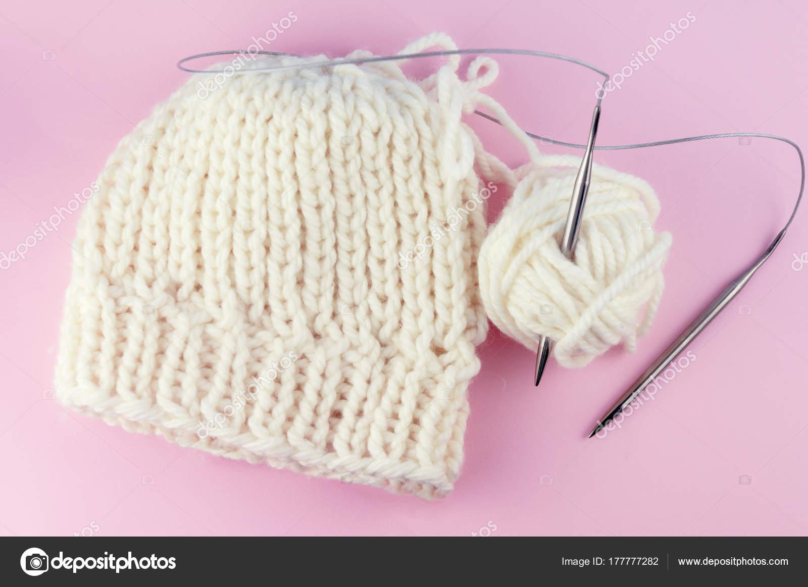 Tejer agujas e hilo sobre un fondo rosa vintage, un casquillo atado ...