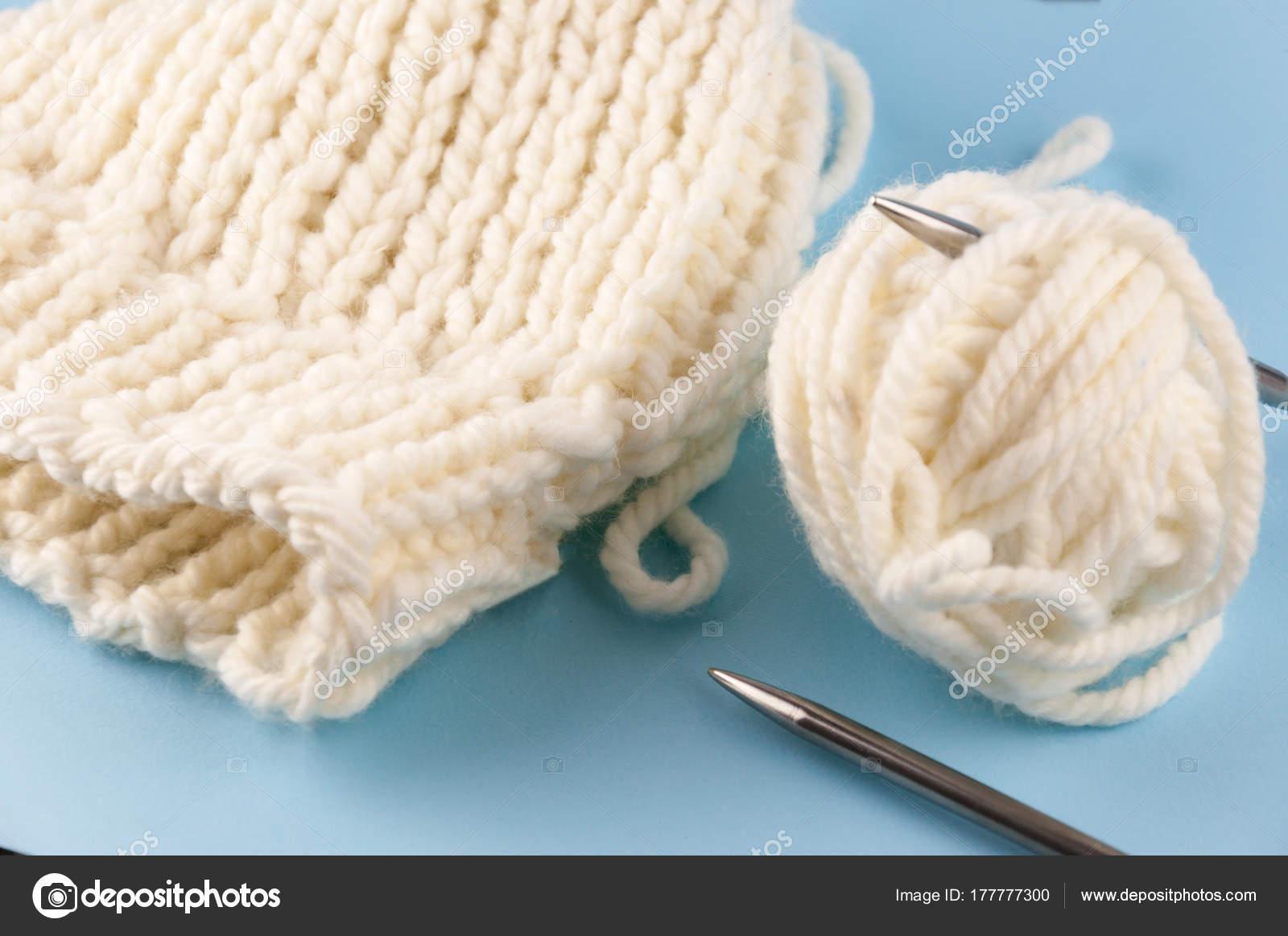 Tejer agujas e hilo sobre un fondo azul vintage, un casquillo atado ...