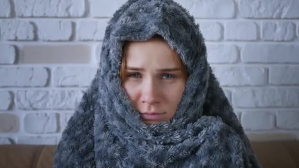 Bedeckt mit grau karierten jungen kaukasischen Frauen, die zu Hause frieren, und kranken Mädchen, die Fieber, Grippe und Fieber haben und in Decken gehüllt sind, frösteln sie drinnen. Nahaufnahme.