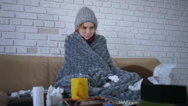 Bedeckt mit grau karierten jungen kaukasischen Frauen in Hut und Schal, die sich zu Hause eiskalt fühlen, krankes krankes Mädchen mit Fieber Grippe-Temperatursymptomen in Decke gehüllt, fröstelt drinnen.