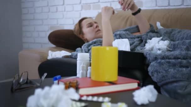 Nahaufnahme junge kaukasische Frau misst die Temperatur auf dem Sofa liegend Fieber zu Hause fühlen sich unglücklich Grippe krank Erwachsene Erkältung Krankheit Person Krankheit Virus Porträt Zeitlupe