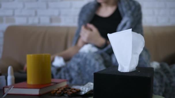junge kaukasische Frau niest nimmt Taschentuch Kopfschmerzen fühlen sich krank zu Hause sitzen auf Sofa Viruserkrankung Erkältung Krankheitssymptom schlechte Temperatur Gesundheit ungesund junge Bettdecke Infektion Pillen Medizin