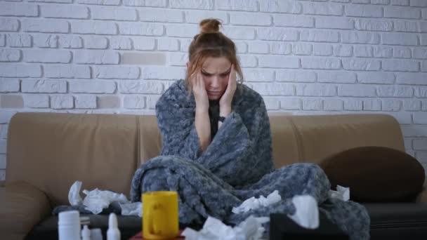 attraktive kranke kaukasische Mädchen in grauer Decke, die auf dem Sofa im Wohnzimmer sitzt. Porträt einer sympathischen, kranken jungen Frau. Furchtbare Migräne. Grippe krank Erwachsene Erkältung Person Krankheit Virusallergie.
