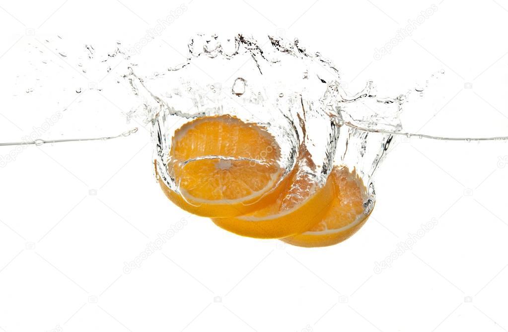 orange fruits making splash in water