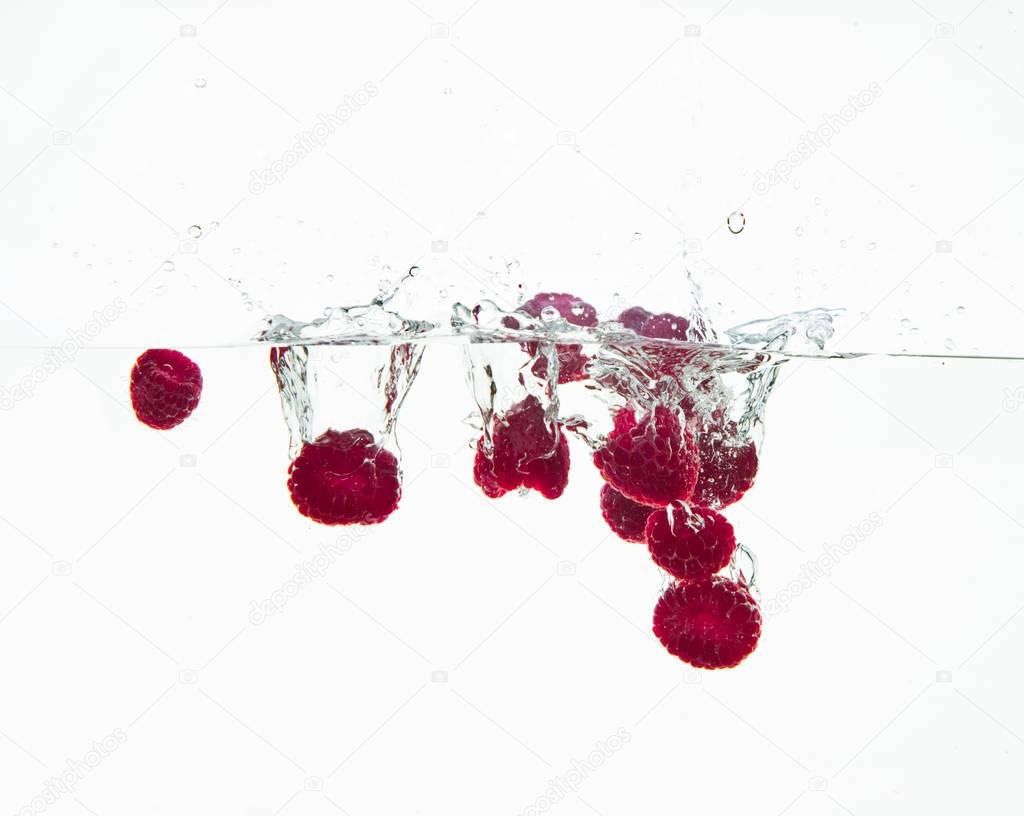 raspberry fruits making splash in water
