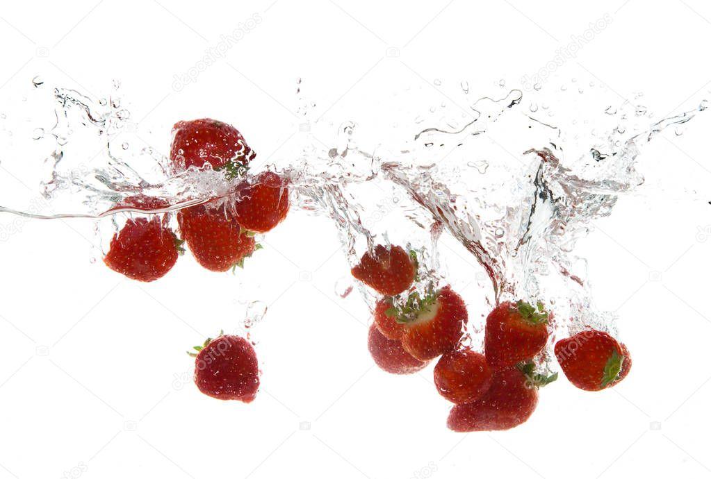strawberry fruits making splash in water